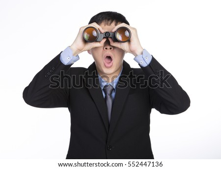 Asian businessman seeing through binoculars and showing shocked expression with mouth opened