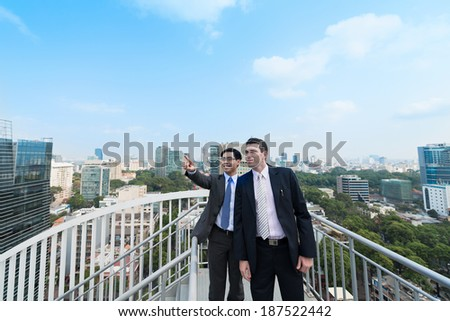 Asian businessman showing something to his colleague, standing on the roof of the building - stock photo