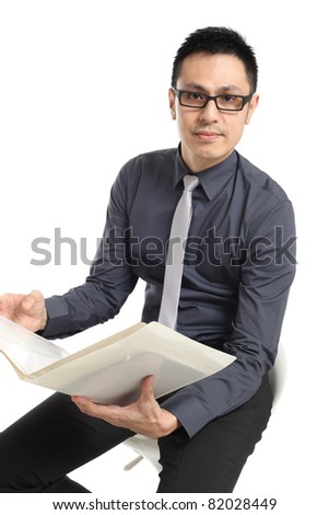 Asian businessman sitting and holding a folder. Isolated on white background - stock photo