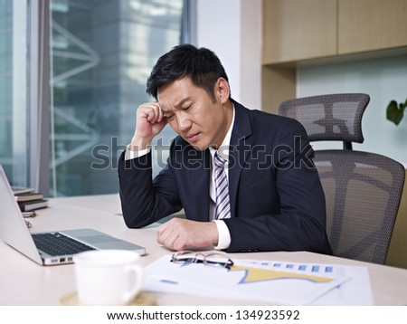 asian businessman sitting and thinking in office, looking frustrated. - stock photo