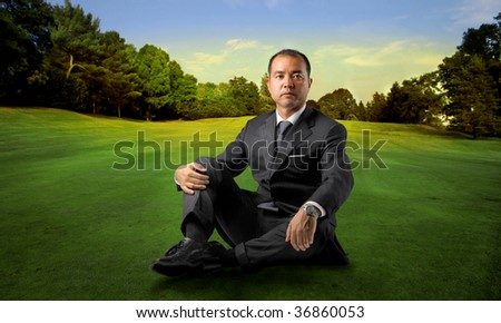 asian businessman sitting in a beautiful park - stock photo