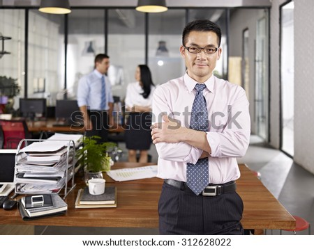 asian businessman standing in office arms crossed with multinational colleagues talking in background. - stock photo
