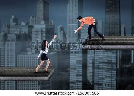 Asian businessman standing on the bridge and helping businesswoman by hand - stock photo