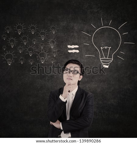 Asian businessman think of big idea with lightbulb background - stock photo