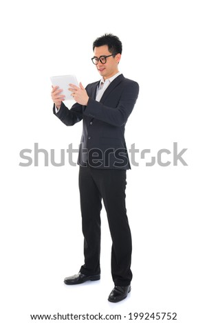 asian businessman using computer tablet full body isolated - stock photo