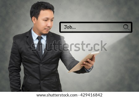 "Asian businessman using the tablet with browsing of Internet searching ""Job"" bar on the wall background, Internet concept"