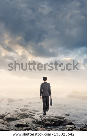 Asian businessman walk into ocean under dramatic cloudy sky. Photo compilation concept about business, dangerous, unknown, blind, future, adventure, risk etc.