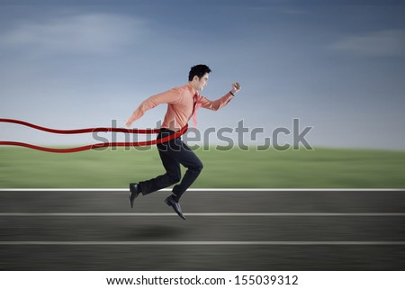 Asian businessman winning a business race outdoor - stock photo