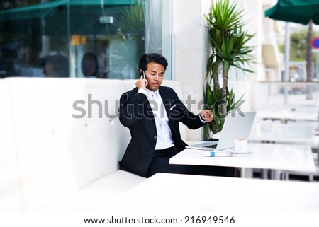 Asian businessman with angry expression on face talking on the smart phone, businessman having a phone talk, young man annoyed, frustrated, pissed off by someone listening on his mobile phone,bad news - stock photo