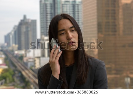 Asian businessman with long hairstyle outdoors talking on mobile phone