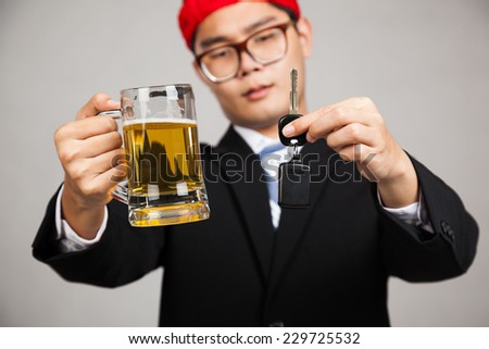 Asian businessman with party hat decide drink or drive with beer and car key on gray background