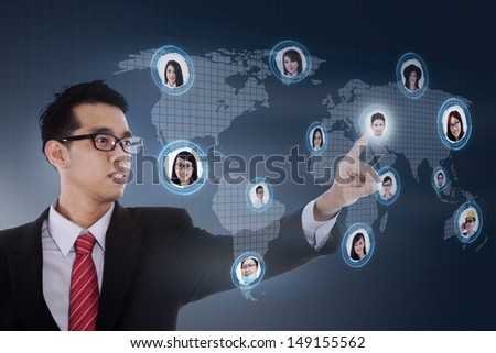 Asian businessman with social network LCD screen against world map background - stock photo