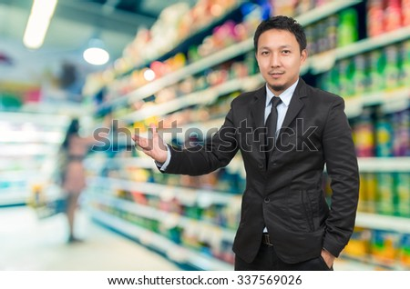 Asian Businessman with welcoming gesture on Supermarket blur background with bokeh background - stock photo
