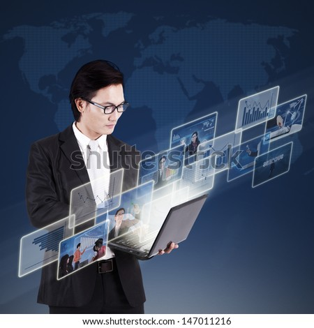 Asian businessman working on his laptop and searching online pictures on blue world map background - stock photo