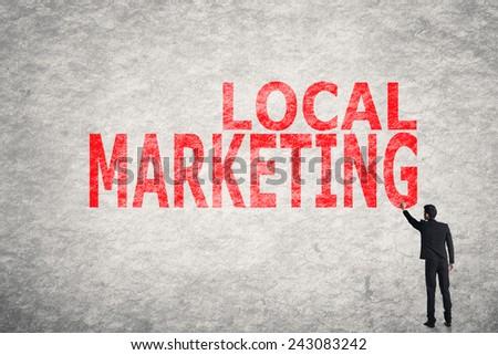 Asian businessman write text on wall, Local Marketing  - stock photo