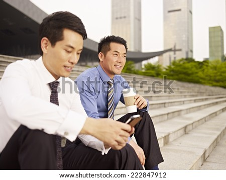 asian businessmen sitting on steps and talking. - stock photo