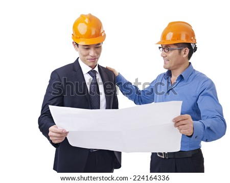 asian businessmen with safety helmet and blueprint. - stock photo