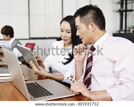 asian businesspeople discussing business in office with help of laptop and tablet computers.