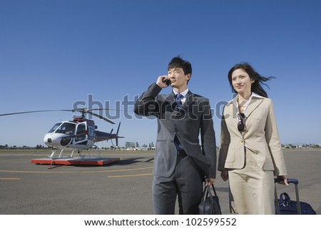 Asian businesspeople waking away from helicopter - stock photo