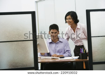 Asian businesswoman and businessman looking at computer - stock photo
