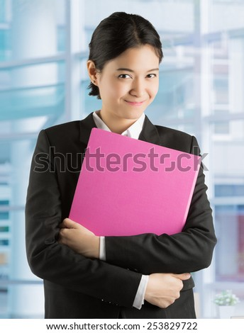Asian businesswoman Are holding a file Expression eyes with hope and confidence in the office - stock photo