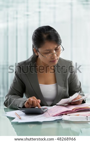 Asian businesswoman checking bills in the office. - stock photo