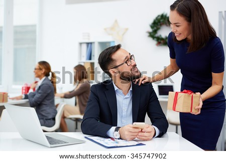 Asian businesswoman giving her boss Christmas present in office - stock photo