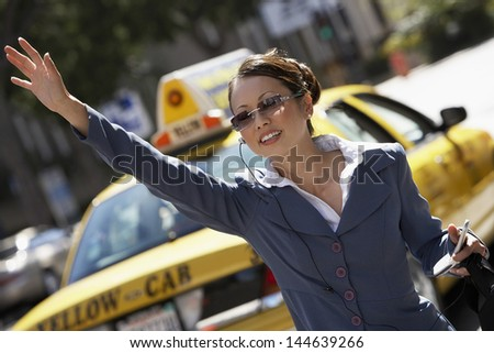 Asian businesswoman hailing cab while using cellphone with hands free device - stock photo