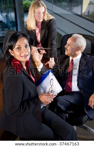 Asian businesswoman in meeting with African American businessman and female colleague - stock photo