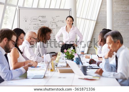 Asian Businesswoman Leading Meeting At Boardroom Table - stock photo