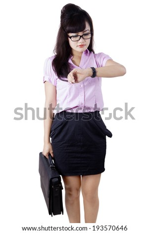 Asian businesswoman looking at her watch. Isolated on white background - stock photo