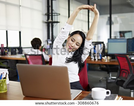 asian businesswoman looking at work on laptop computer with satisfaction and stretching arms in the air. - stock photo