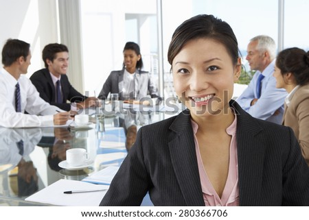 Asian Businesswoman Sitting Around Boardroom Table With Colleagues - stock photo
