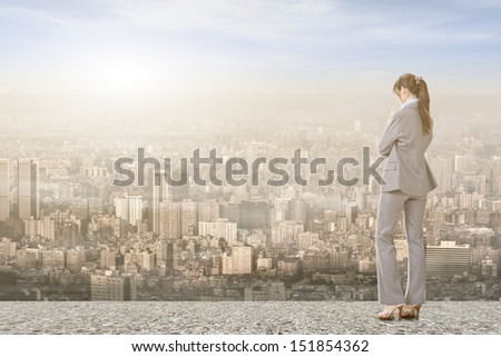 Asian businesswoman standing on the roof and looking at city, with sunrise or sunset. - stock photo