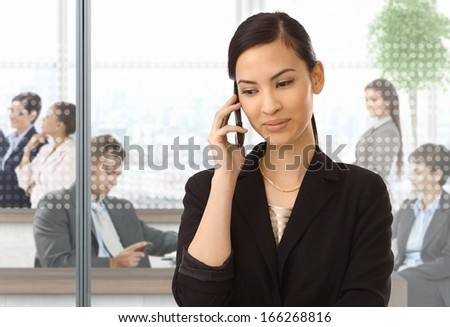 Asian businesswoman using mobile phone at office, smiling.