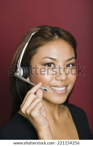 Asian businesswoman wearing headset - stock photo