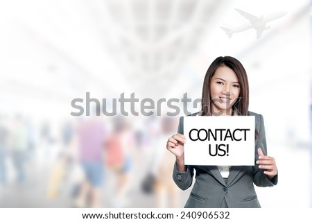 asian businesswoman with long hair holding a sign board with a contact us ,Mixed Asian / Caucasian businesswoman. - stock photo