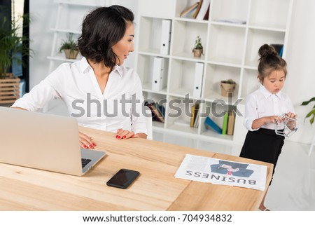 asian businesswoman working while her adorable daughter playing behind in modern office