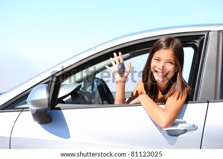 Asian car driver woman smiling showing new car keys and car. Mixed-race Asian and Caucasian girl. - stock photo
