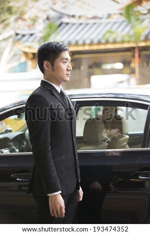 Asian chauffeur or business man standing next to a luxury car. Chinese heritage temple in background.