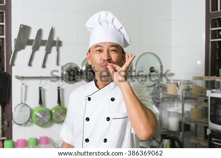 """Asian chef smiling and showing """"delicious"""" on the kitchen background.  - stock photo"""