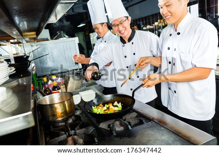 Asian Chefs in Hotel or Restaurant Kitchen cooking and finishing dishes - stock photo