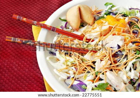 Asian chicken salad with chopsticks and a fortune cookie. - stock photo