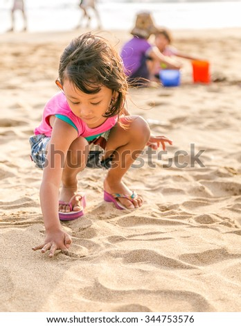 Asian Child Enjoy Drawing on The White  Beach Sand, Selective Focus on Hand - stock photo