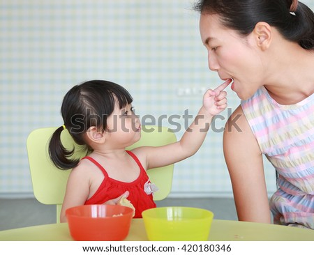 Asian Child girl and mother eating boiled egg at living room