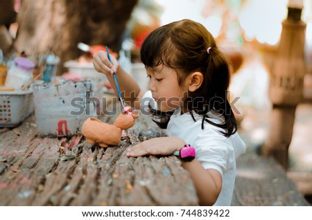 Asian child girl Sitting on a wooden chair painting animal Clay doll She intended