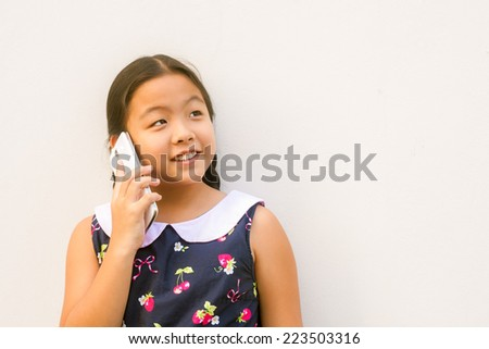asian child girl  smiling  face hold and calling,receive  on smart phone,touch screen, tablet, on gray wall background. - stock photo