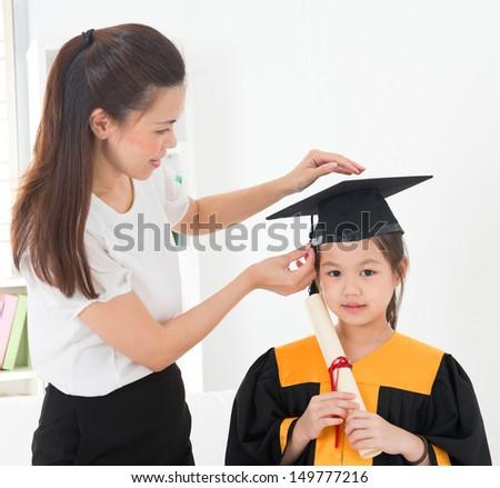 Asian child graduation, teacher adjusting cap for student indoor. - stock photo