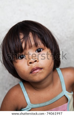 Asian child living in poverty - young Filipino girl against wall - stock photo