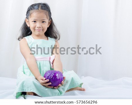 asian child smiling And holding Purple cabbage. Food needed for children, concept.